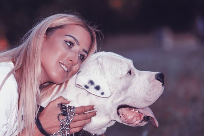 A jovem mulher bonita aprecia seu cão no parque - Dogo Argenti fotografia de stock