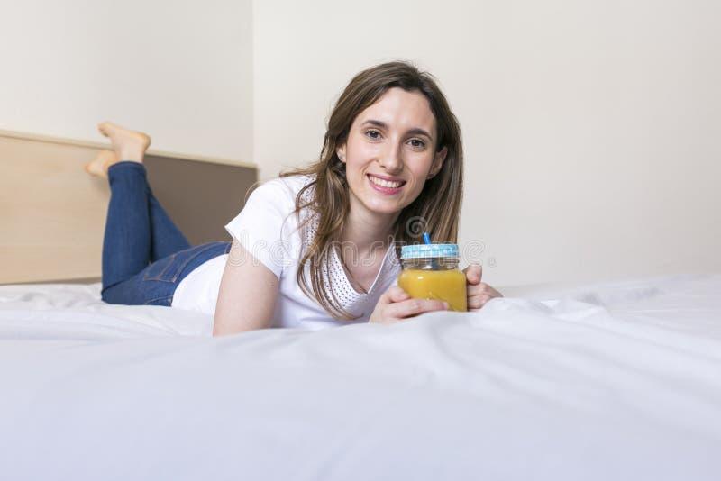 Jovem mulher bonita apreciando um suco de laranja saudável em casa fotos de stock royalty free
