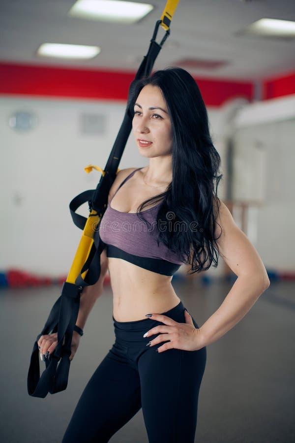 Jovem mulher bonita apta que faz a ioga da mosca que estica exercícios com as correias da aptidão do trx na sala de aula branca d fotos de stock