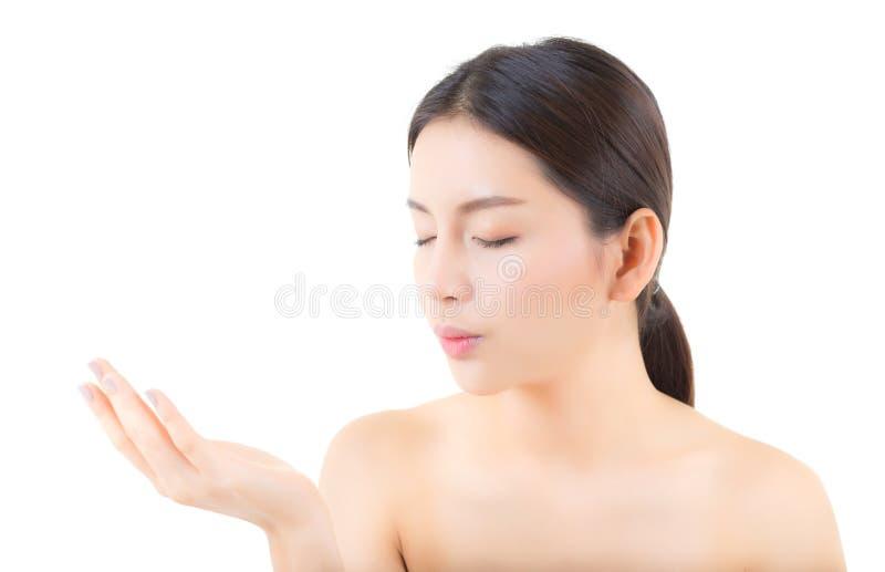 Jovem mulher bonita asiática que mostra com a pele limpa saudável que apresenta a algo o espaço vazio da cópia na mão isolada imagens de stock