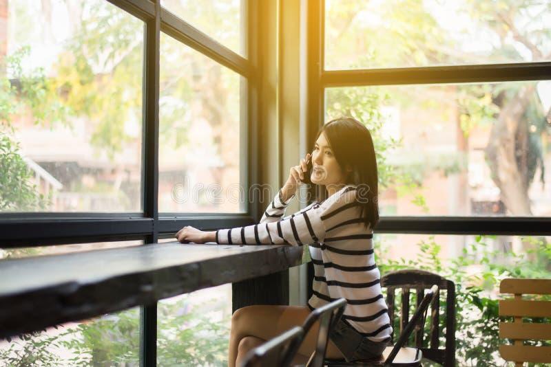 Jovem mulher bonita asiática que usa o telefone celular no restaurante moderno, feliz e encantador, pensamento do positivo fotos de stock