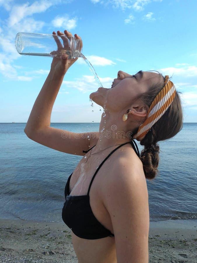 A jovem mulher bonita bebe a agua potável da garrafa imagem de stock