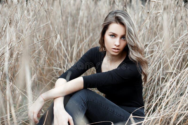 Jovem mulher bonita bonito moderna na roupa à moda que senta-se na grama seca do outono fora Louro atrativo bonito fotografia de stock royalty free