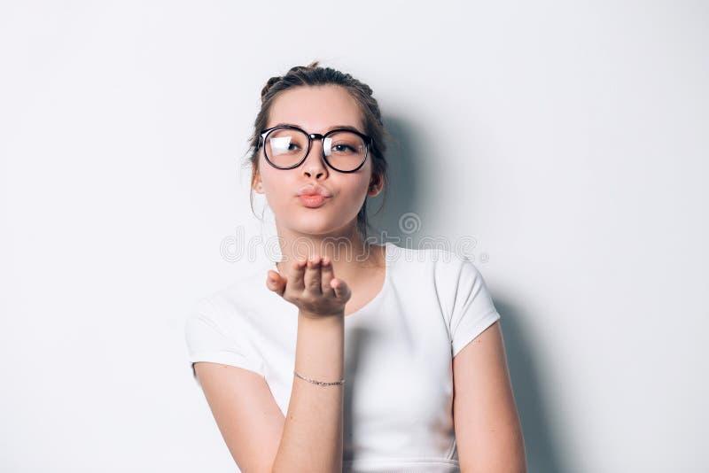Jovem mulher bonita bonito nos óculos de sol redondos que estão e que enviam o beijo em um fundo branco imagem de stock