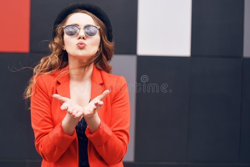 Jovem mulher bonita bonito nos óculos de sol, revestimento e chapéu vermelho da forma, posição e beijo da emissão sobre o fundo v fotos de stock