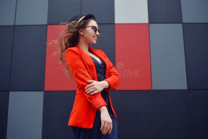 Jovem mulher bonita bonito nos óculos de sol, revestimento vermelho, chapéu da forma, estando sobre o fundo abstrato exterior Mod fotografia de stock royalty free
