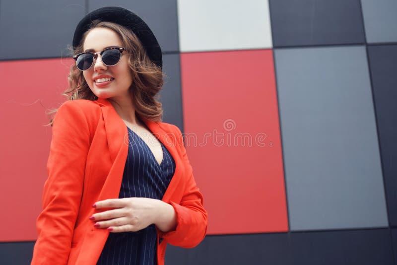 Jovem mulher bonita bonito nos óculos de sol, revestimento vermelho, chapéu da forma, estando sobre o fundo abstrato exterior Mod fotos de stock royalty free