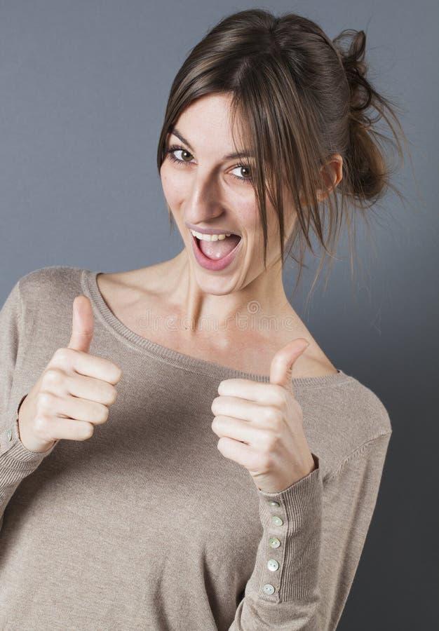 Jovem mulher bonita chique que ri com polegares acima imagem de stock royalty free