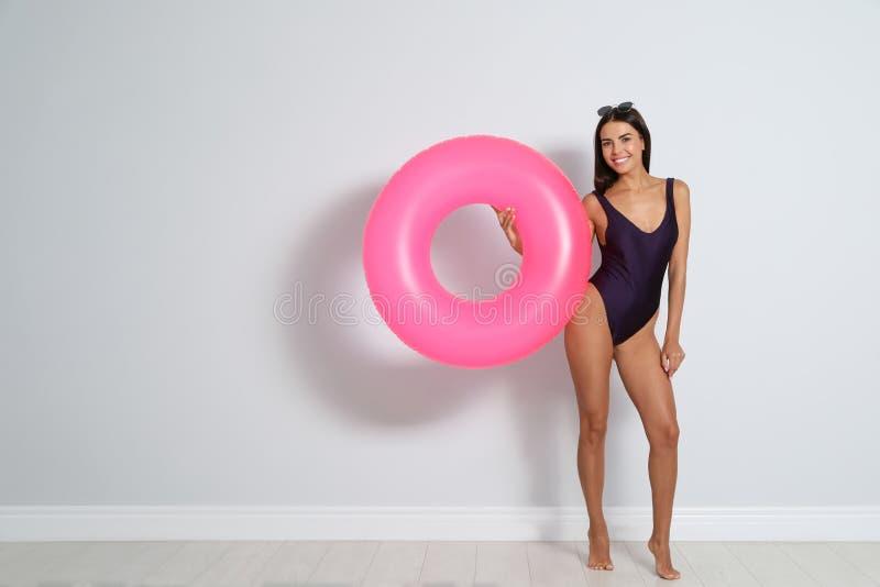 Jovem mulher bonita com anel inflável brilhante perto da parede leve, espaço fotos de stock