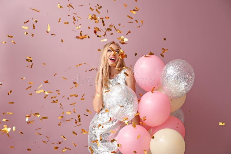 Jovem mulher bonita com balões de ar e confetes de queda contra o fundo da cor fotografia de stock