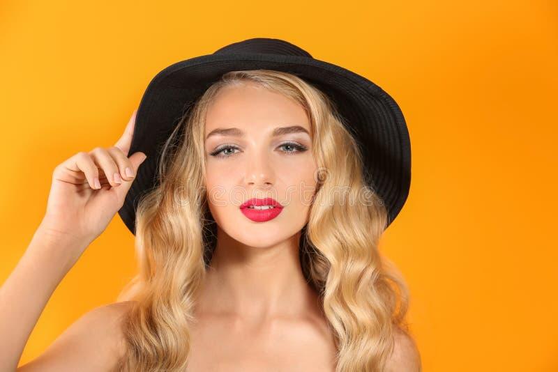 Jovem mulher bonita com batom e o chapéu vermelhos brilhantes no fundo da cor foto de stock