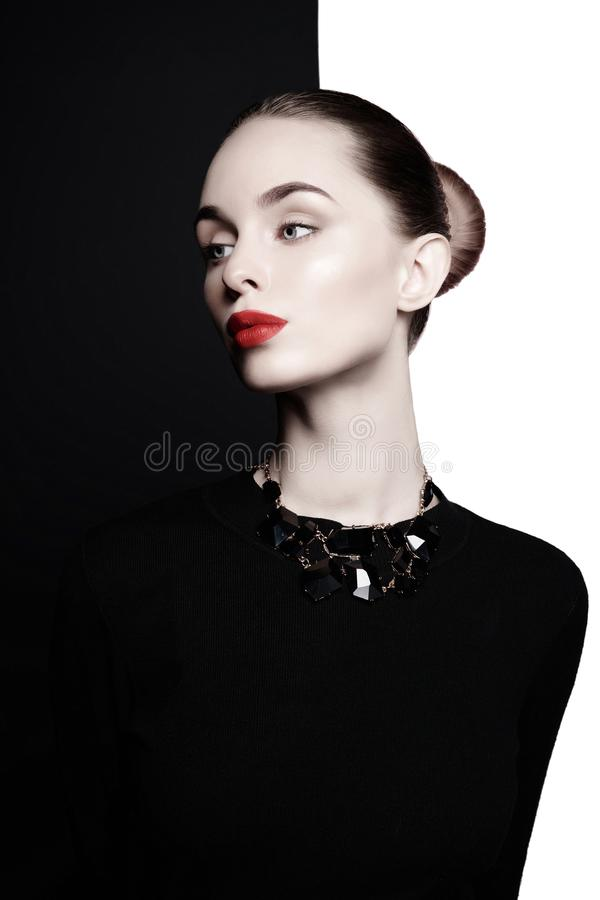 A jovem mulher bonita com bijouterie preto levanta no est?dio imagens de stock