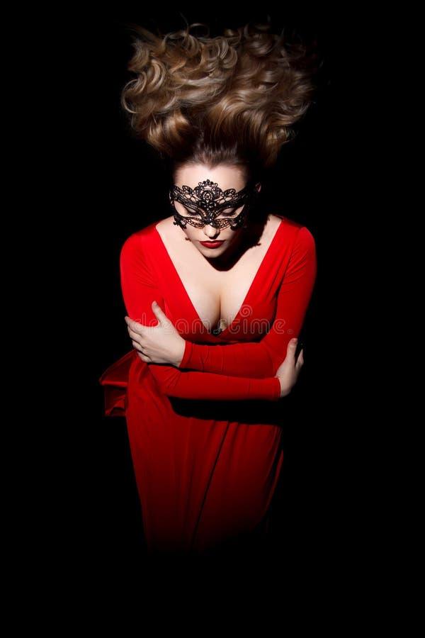Jovem mulher bonita com cabelo de sopro em um vestido vermelho imagem de stock royalty free