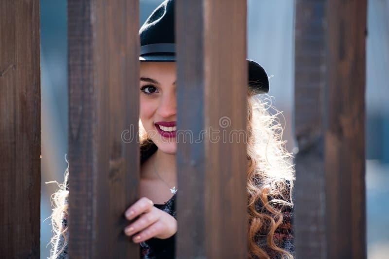 Jovem mulher bonita com cabelo encaracolado atrás do colunas de madeira fotografia de stock