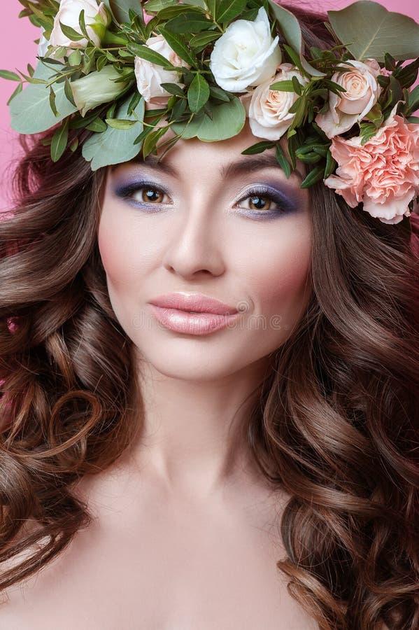 A jovem mulher bonita com cabelo encaracolado e a flor envolvem-se em sua cabeça na menina cor-de-rosa da beleza do fundo com o p imagem de stock royalty free