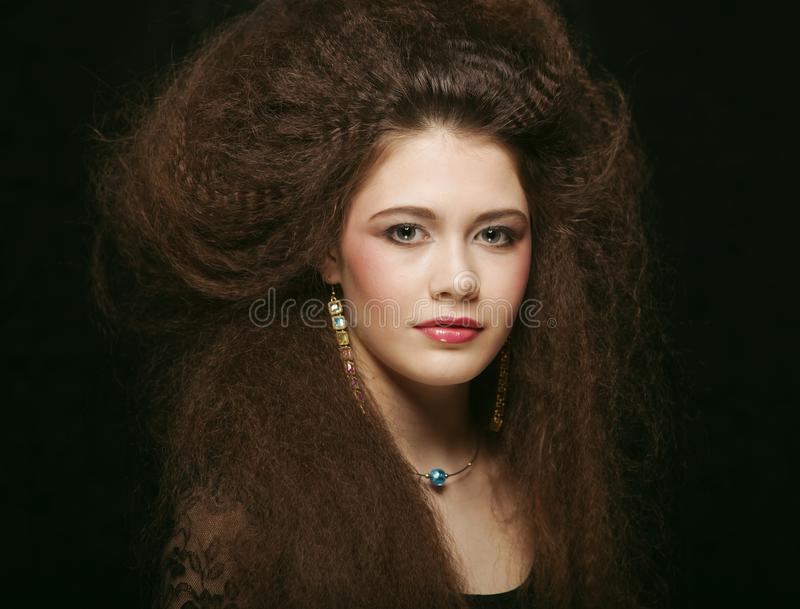 A jovem mulher bonita com cabelo encaracolado e a noite preparam Joia e conceito da beleza Foto da arte da forma fotografia de stock royalty free
