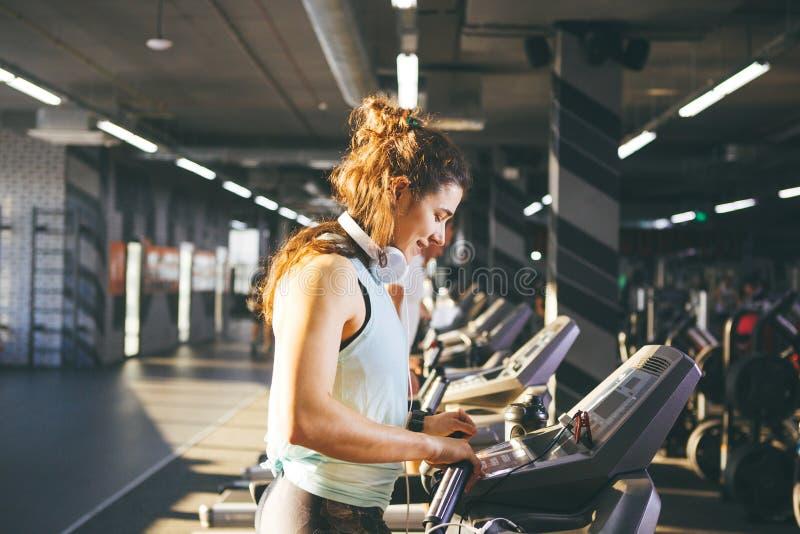 A jovem mulher bonita com cabelo encaracolado luxúria na veste e nas caneleiras corre no gym na escada rolante, na cardio- máquin imagem de stock
