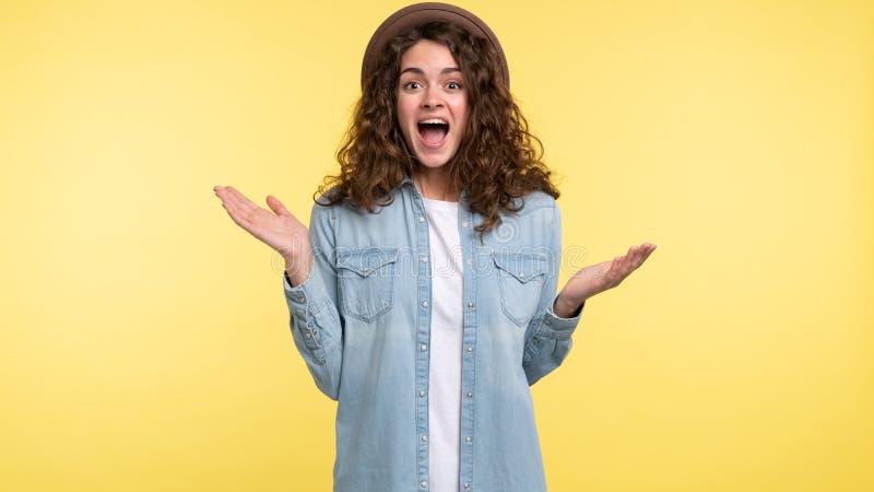 Jovem mulher bonita com cabelo encaracolado que grita em uma surpresa e obtida feliz, sobre o fundo amarelo imagens de stock