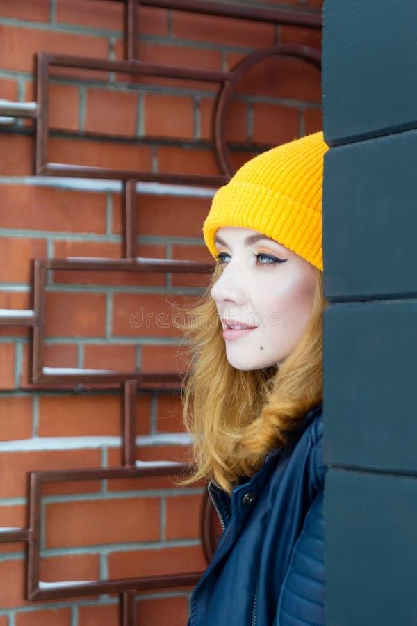 A jovem mulher bonita com cabelo louro e olhos azuis em um chapéu de confecção de malhas amarelo está olhando do canto imagem de stock