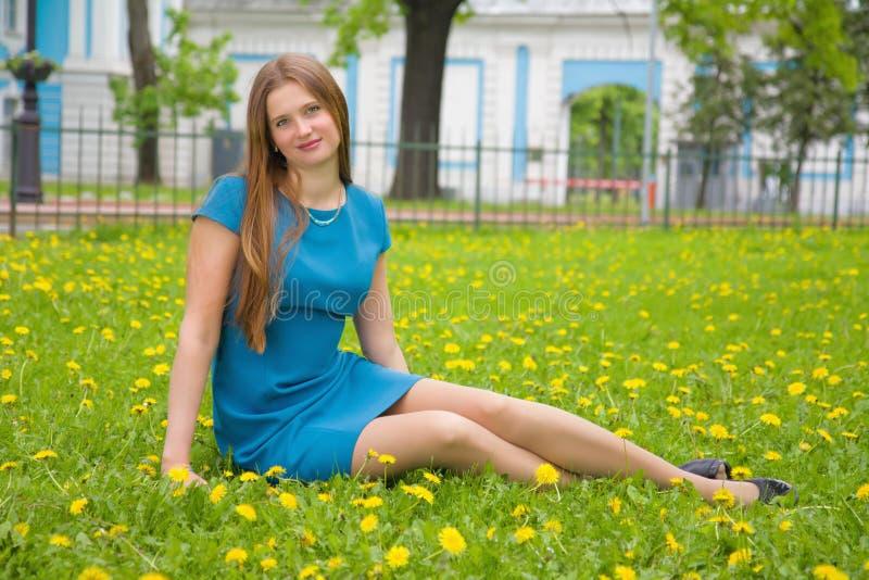 Jovem mulher bonita que senta-se no prado da mola fotografia de stock