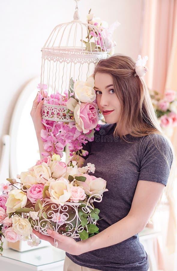 Jovem mulher bonita com cabelo louro longo, olhos azuis, gaiola de florescência, t-shirt vestindo imagens de stock