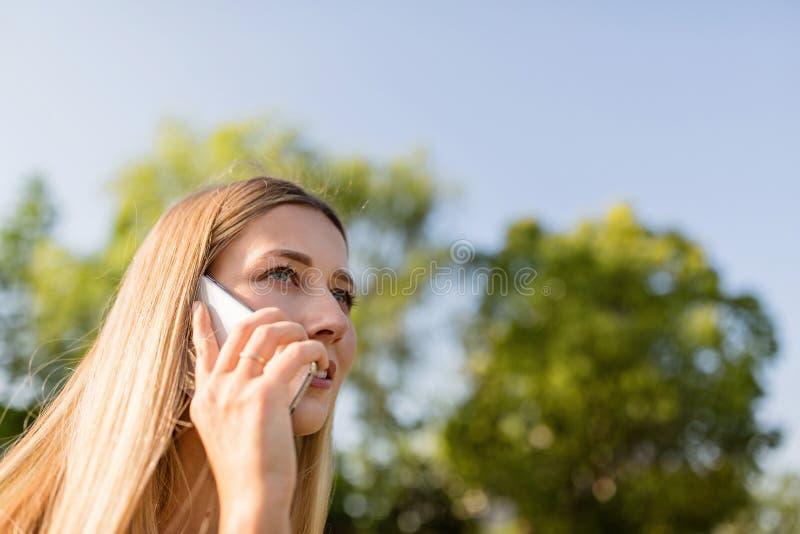Jovem mulher bonita com cabelo louro usando o telefone celular exterior Menina ? moda que faz o selfie imagens de stock royalty free