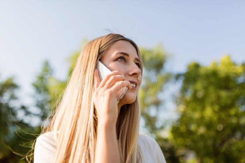 Jovem mulher bonita com cabelo louro usando o telefone celular exterior Menina ? moda que faz o selfie foto de stock royalty free