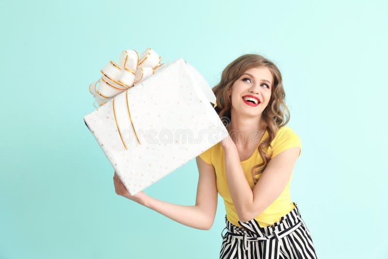Jovem mulher bonita com a caixa de presente no fundo da cor imagem de stock royalty free