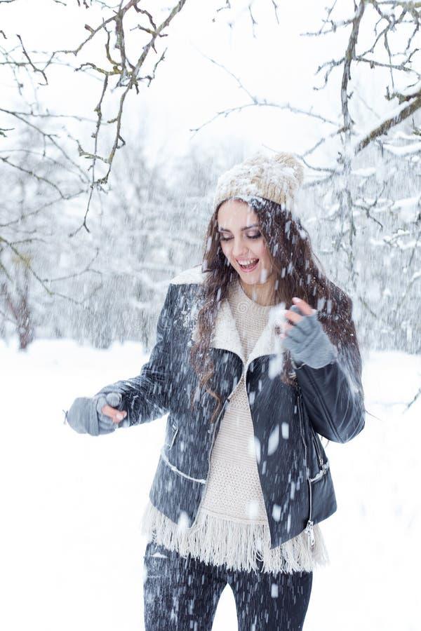 Jovem mulher bonita com caminhada longa do divertimento do cabelo escuro nas madeiras do inverno e jogo com neve em um chapéu do  fotos de stock