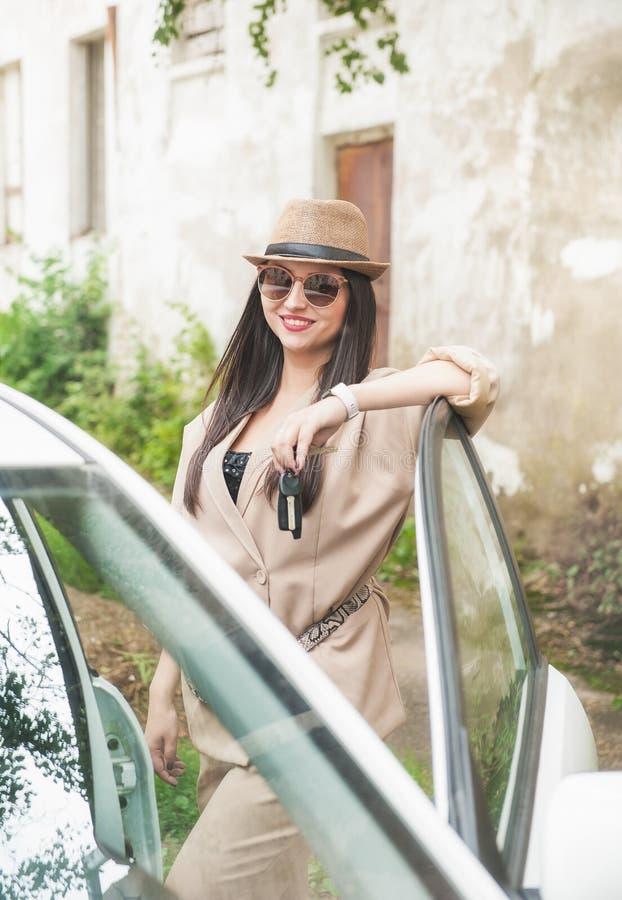 Jovem mulher bonita com chapéu e monóculos no carro fotografia de stock