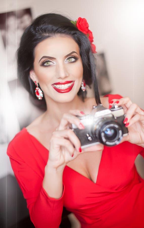 Jovem mulher bonita com composição criativa e o penteado que tomam fotos com uma câmera Morena atrativa elegante imagem de stock royalty free