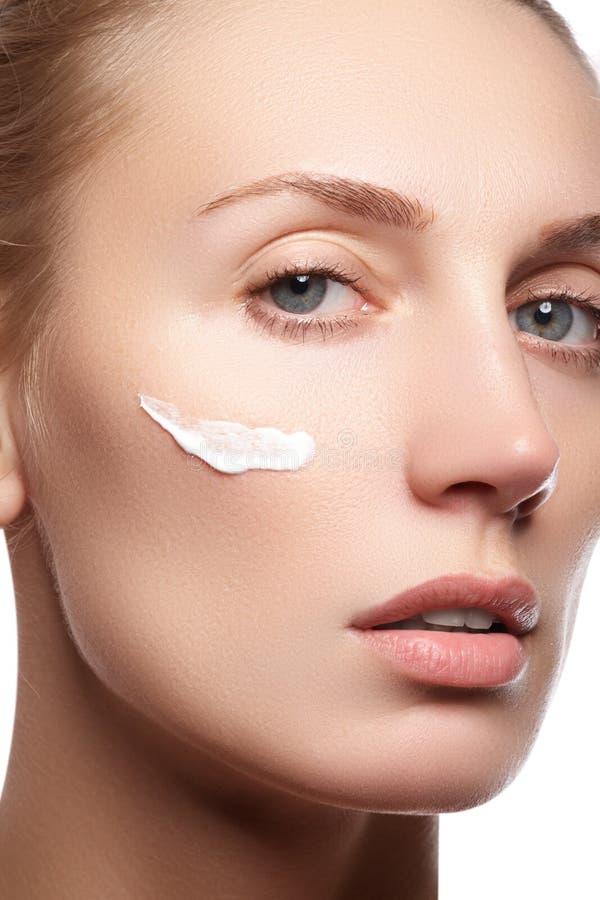 Jovem mulher bonita com creme cosmético em um mordente fotos de stock