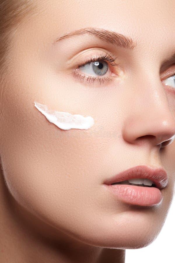 Jovem mulher bonita com creme cosmético em um mordente foto de stock