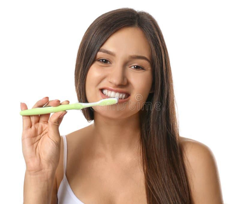 Jovem mulher bonita com a escova de dentes no fundo branco fotos de stock royalty free