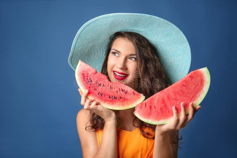 Jovem mulher bonita com fatias de melancia saboroso no fundo da cor fotos de stock royalty free