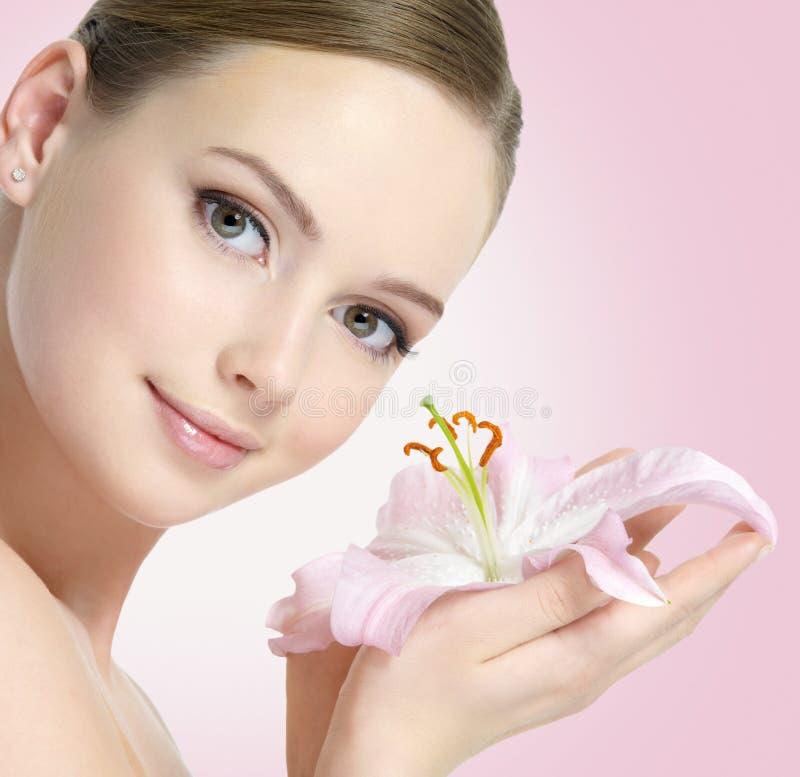 Jovem mulher bonita com a flor do lírio nas mãos imagens de stock royalty free