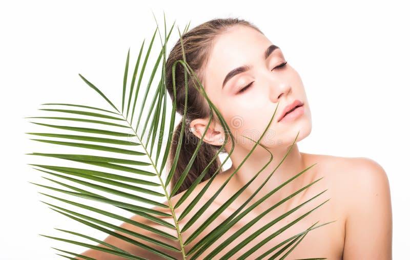 Jovem mulher bonita com folhas de palmeira no fundo branco Conceito do cuidado de pele foto de stock royalty free