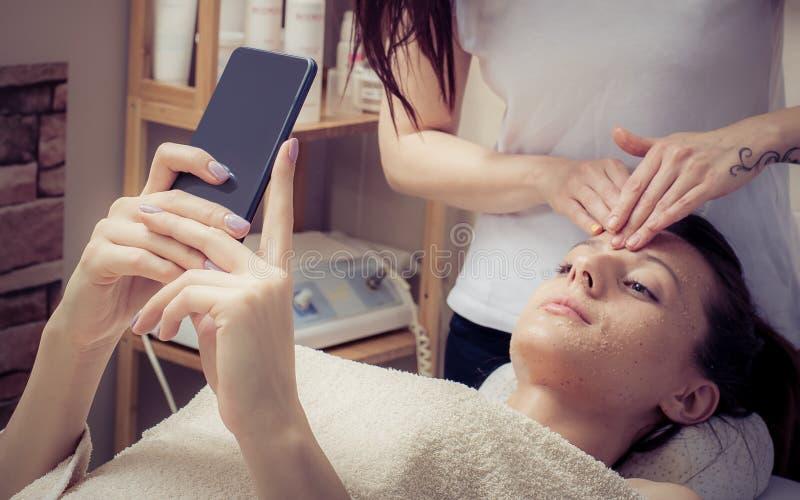 Jovem mulher bonita com máscara facial usando o smartphone no salão de beleza foto de stock