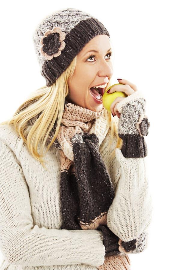 Jovem mulher bonita com a maçã, olhando acima. Estilo do inverno fotos de stock royalty free