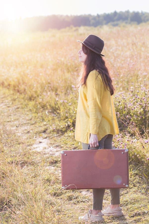 Jovem mulher bonita com a mala de viagem e o chapéu negro marrons do vintage na estrada do campo durante o por do sol do verão foto de stock royalty free