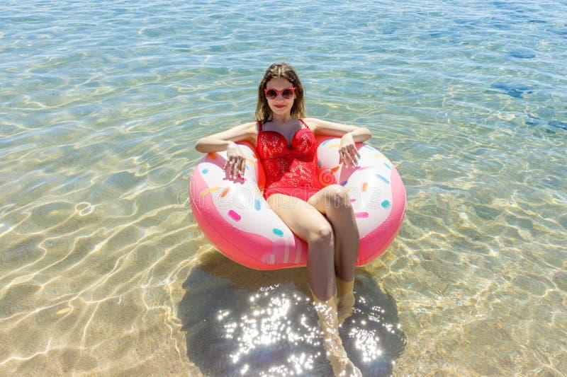 Jovem mulher bonita com o anel inflável que relaxa no mar azul fotografia de stock royalty free