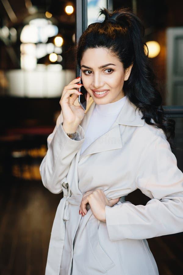 Jovem mulher bonita com o cabelo escuro amarrado na cauda de pônei e agradável foto de stock royalty free