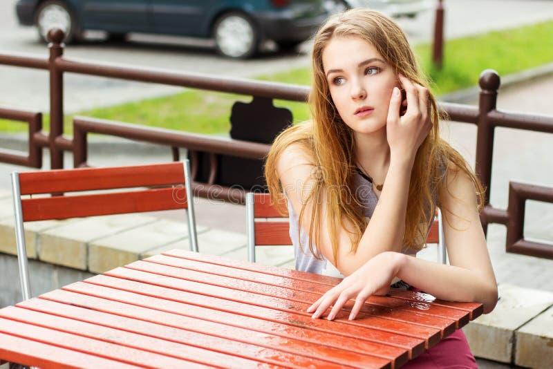 Jovem mulher bonita com o cabelo vermelho longo que senta-se em um café na rua na cidade após uma chuva e que espera meu café imagem de stock