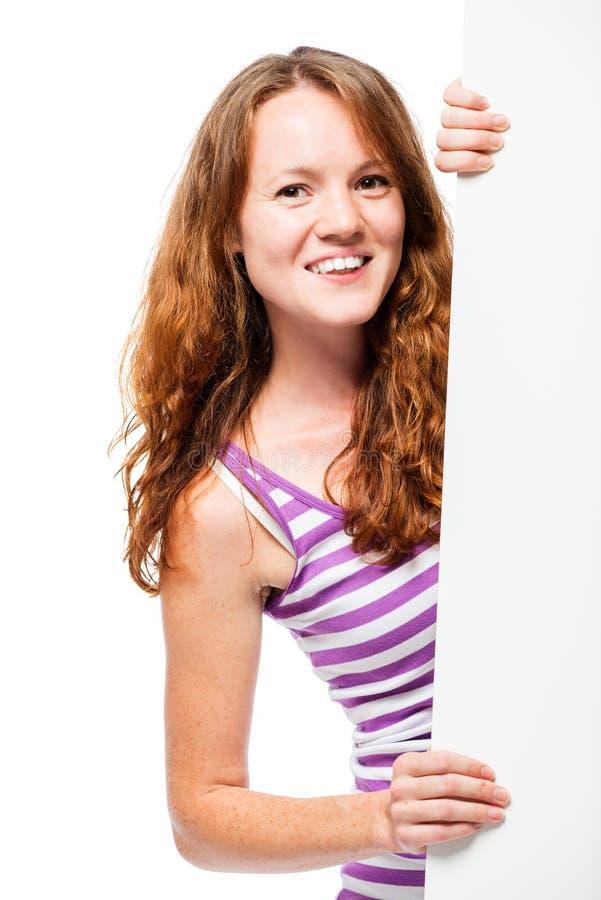 Jovem mulher bonita com o cartaz vazio branco para anunciar imagens de stock royalty free