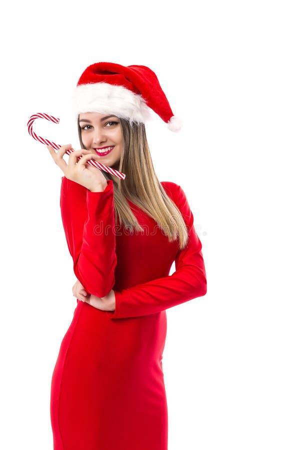 A jovem mulher bonita com o chapéu de Santa que guarda uns doces festivos pode fotos de stock royalty free