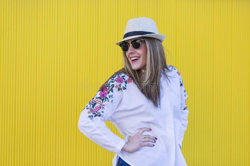 Jovem mulher bonita com o chapéu e os óculos de sol que têm o divertimento amarelo imagens de stock