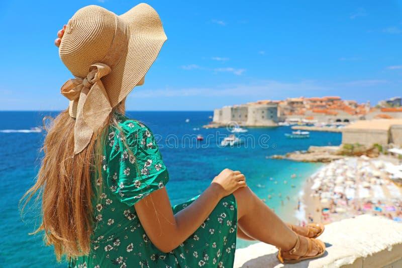 Jovem mulher bonita com o chapéu que senta-se na parede que olha a cidade velha panorâmico impressionante de Dubrovnik na Croácia imagem de stock
