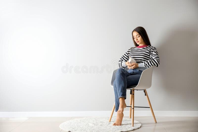 Jovem mulher bonita com o coelho bonito que senta-se na cadeira perto da parede leve fotos de stock royalty free