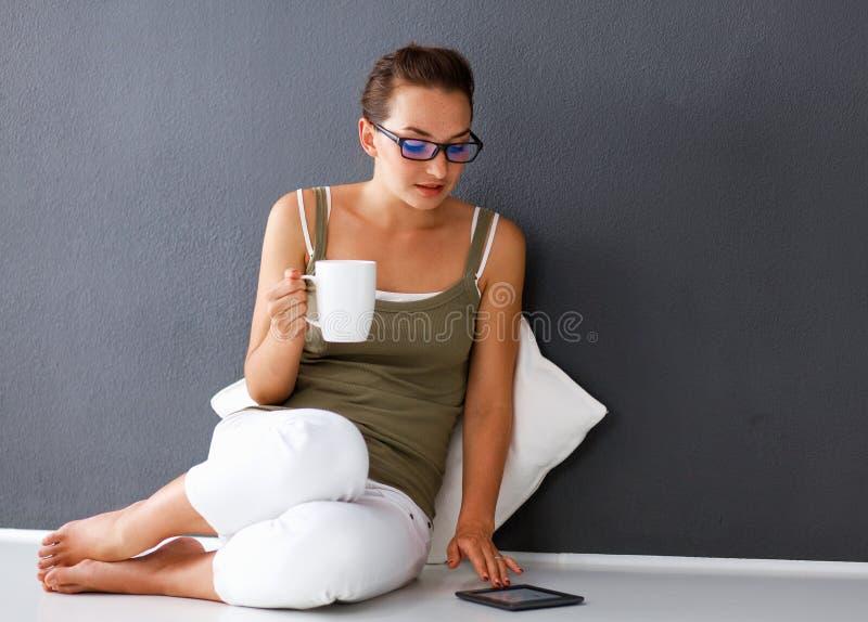 Jovem mulher bonita com o copo do chá usando o tablet pc ao sentar-se no assoalho em casa imagem de stock royalty free