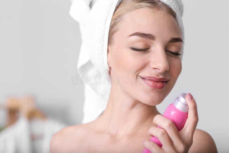 Jovem mulher bonita com o desodorizante no banheiro foto de stock
